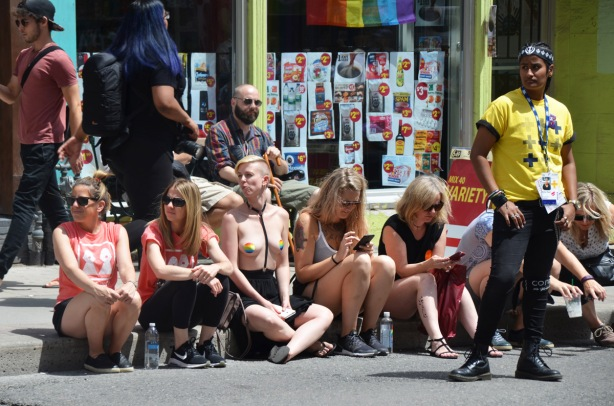 a group of people sittingo n the sidewalk on Yonge street as they watch the Dyke March. One woman is topless, two women are on cellphones