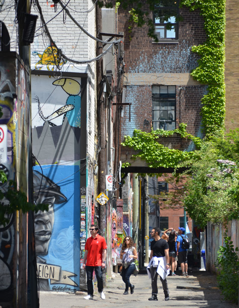 people walking down Graffiti Alley on a sunny afternoon