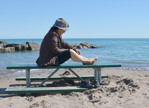a woman sits on top of a picnic table onthe beach because the sand comes up to the level of the seats, lake and rocks in the background.