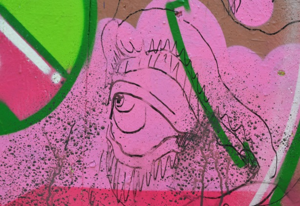 a drawing of a large eye on top of pink and green street art