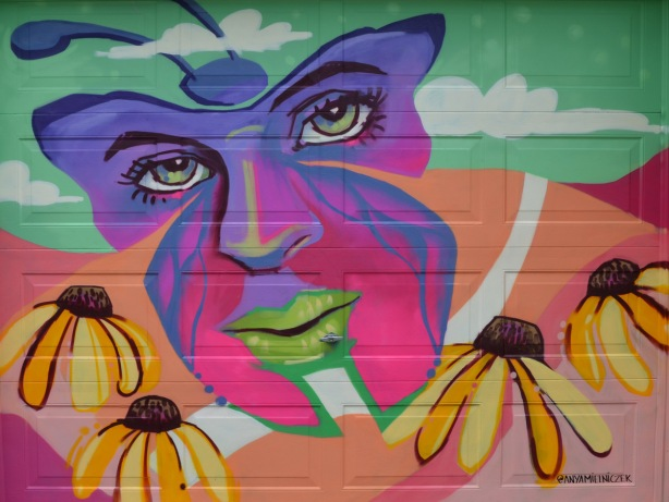 a mural on a garage door in an alley, part of butterflyways project - a pink and purple butterfly that looks like a face, with daisies