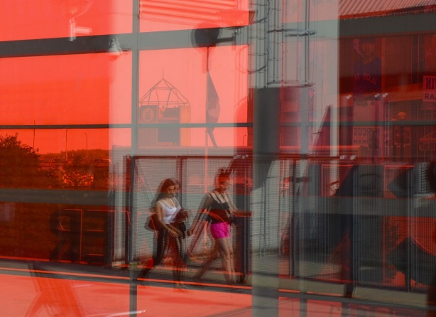 reflected in the red glass of the entrance to the CN tower are two women walking