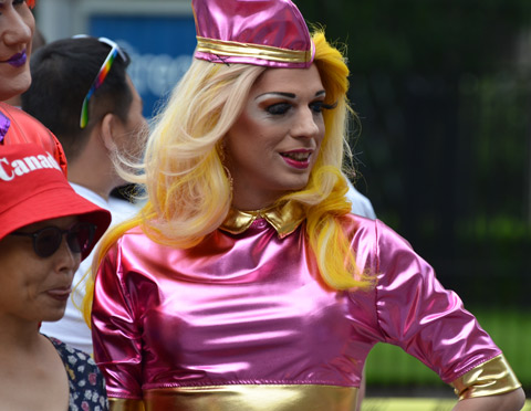 a person in a blond wig and magenta shiny top and matching hat, an Asian woman is having her picture taken as well.