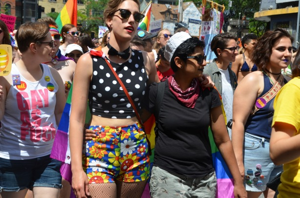 people walking in the dyke march, colourful clothes, floral shorts, polka dot top, sailor hat, flags, beads,