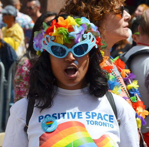 a woman wearing blue rimmed sunglasses and rainbow paper flowers in her hair is looking directly at the camera and shouting. She has a t shirt on that says Positive Space toroto