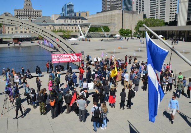 lookng down from the upper level, people at a protest rally at Nathan Phillips square, Toronto flag in the foreground