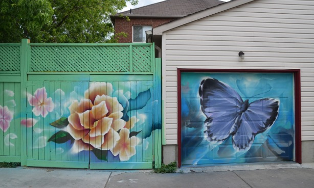 a mural on a garage door in an alley, part of butterflyways project - two adjacent garage doors, the left one is painted on a light green fence and is a flower in pale oranges and beiges. On the right is a purple butterfly