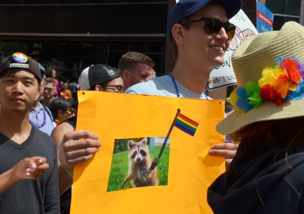 a young man holds an orange sign .. on the sign is a picture of a raccoon holding a rainbow flag with the words happy pride 2017