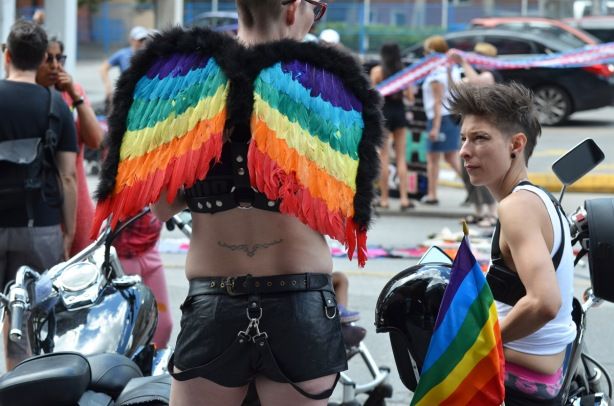 waiting for the dyke march to begin, two people by their motorcycle, one is in leather shorts and has angel wings made of rainbow coloured feathers