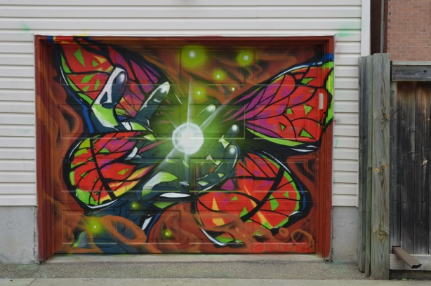 a mural on a garage door in an alley, part of butterflyways project - a red butterfly with a bright light in the center of it.