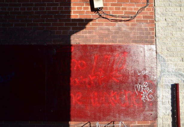 partly hidden by shadow, brick wall with reddish painted square on it.