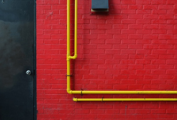 red wall with black door and yellow pipes
