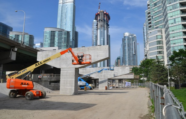 "two ""cherry pickers"" parked in front of new bents being constructed for a new ramp for the Gardiner Expressway"