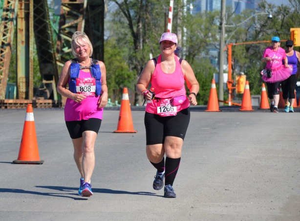 two women smiling as they run in the Run Like a Diva half marathon. on the left is Diva Debbie, bib 808 and on the right is bib number 1266, Diva Sandy