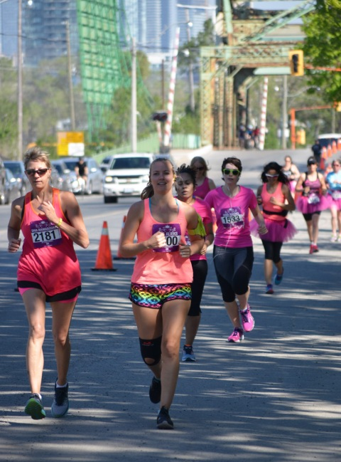 a group of women running on Cherry St in the Port Lands as part of the Run Like a Diva 5k run.