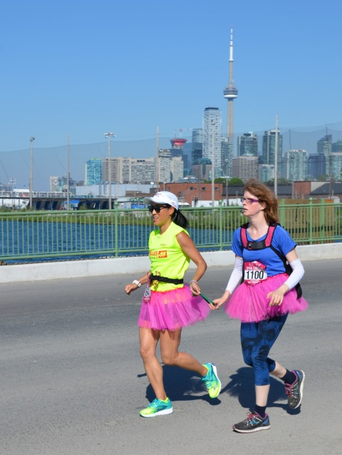 two women running together in the Run Like a Diva half marathon run, both are wearing pink tutus, they are connected with a piece of rubber that they are each holding on to. on the right is Diva Chelsea, bib number 1100.