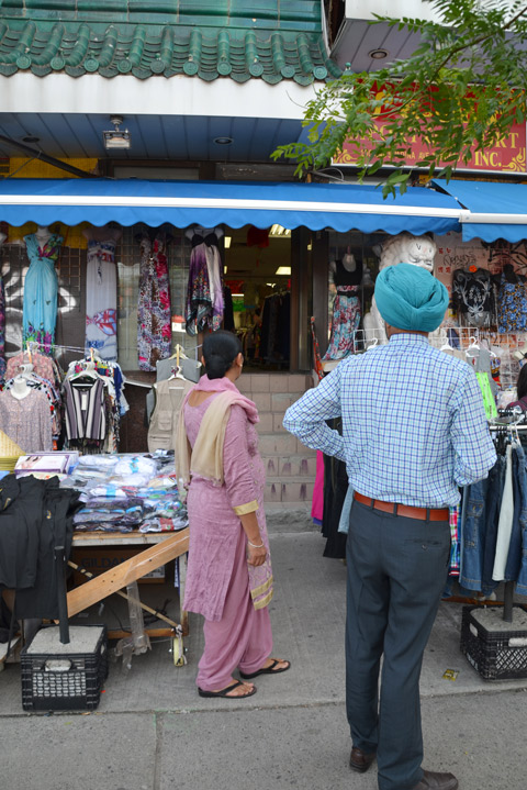 a woman in a pink saree and a man in a turquoise turban stand outside the entrance to a clothing store on Spadina