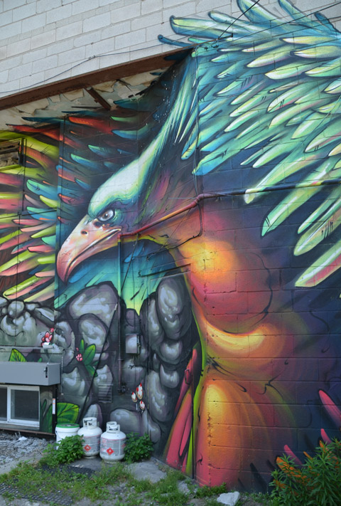 part of a large colourful mural by clandestinos smoky and shalak - a large bird with its wings out stretched getting ready to take off