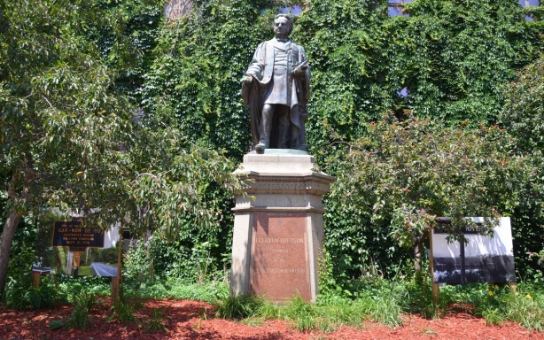 statue of Egerton Ryerson in a small garden with shrubs and small trees. Two large photographs also in the picture, one on each side of the statue