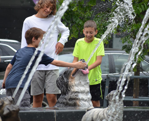 Three boys playing with the water spouting out of a dog's (sculpture) mouth and into a fountain. One is spraying the other while a third watches