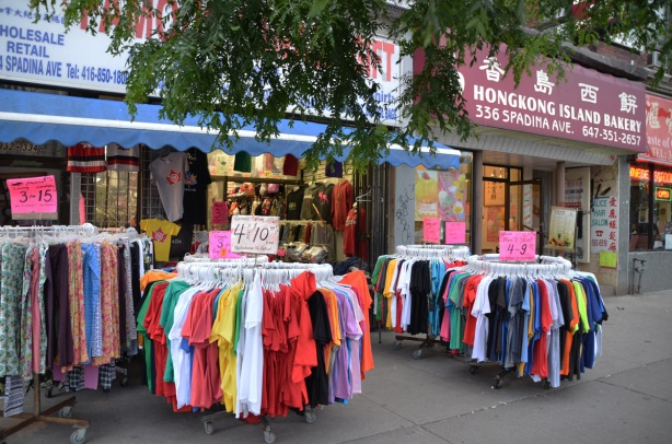 racks of pants and t-shirts for sale, on the sidewalk outside a store