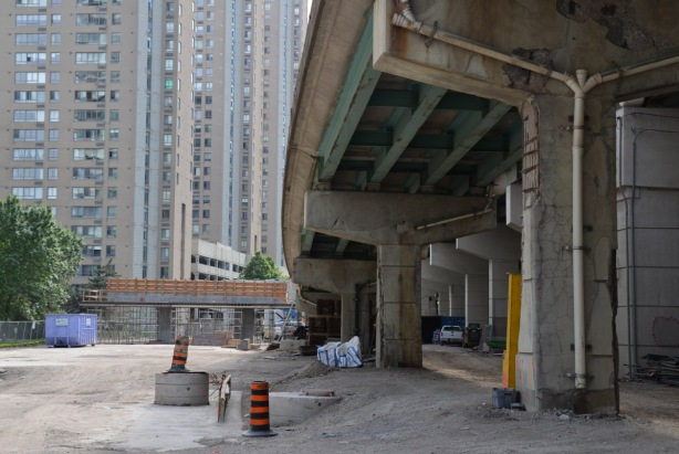 under one of the Gardiner Expressway ramps, with new bents being built for a new ramp in the background.