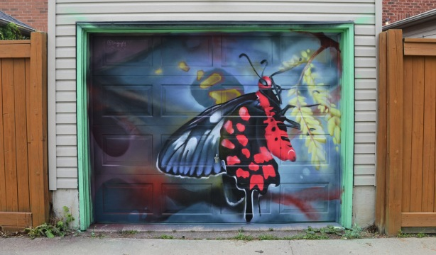 a mural by smugugly on a garage door in an alley, part of butterflyways project - a red, black and bluish butterfly