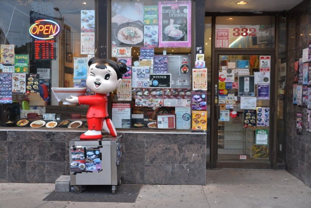 sculpture of a little Asian girl dressed in red holding a large soup bowl, standing outside a restaurant with a lot of signs in the window and on the door