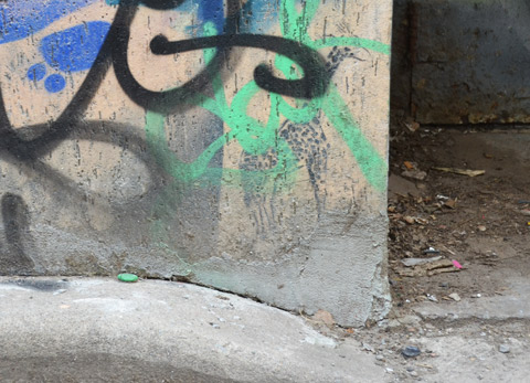 a small stencil of a giraffe stands at the bottom corner of a wall