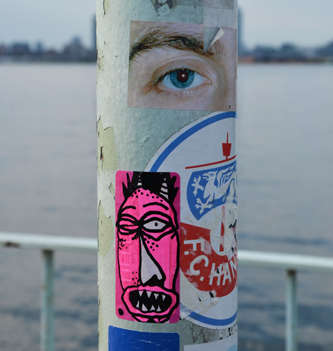 stickers on a pole. One is a photo of an eye and eyebrow and the other is a drawing of a very pink face with crooked nose and open mouth with teeth showing.