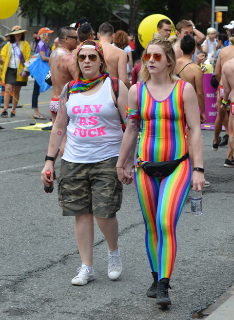 two women walk together holding hands. one has a white shirt that says gay as fuck in pink letters and the other is wearing a sleeveless body suit in rainbow stripes