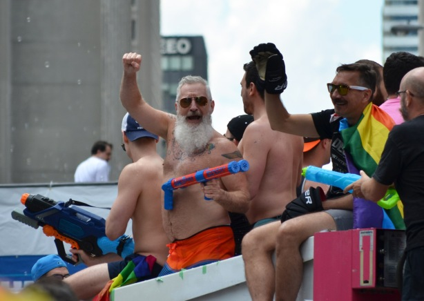 men holding super soakers on top of a pride parade float