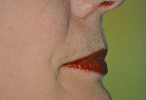 colour photo of close up of a woman's face, just mouth, bottom part of nose and some cheek. She is wearing bright red lipstick