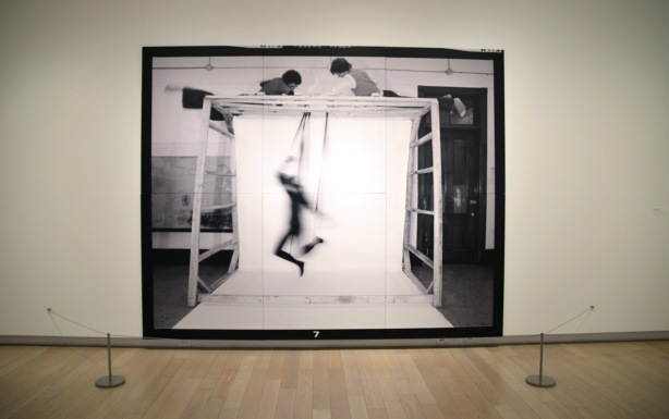 large black and white photograph in a gallery, two men on top of a large frame are controlling the movements of a human puppet