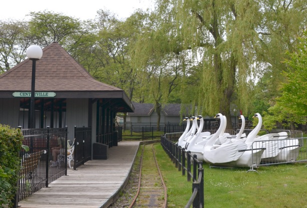large white boats in the shapes of swans are stored on shore, beside a train track and station for the Centreville amusement park. It looks like the swans are waiting for a train