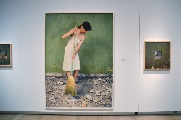 large photo in a gallery of a women dressed just in a long slip, sweeping up debris from the floor. Debris is bits and chunks of plaster that have been removed from the wall