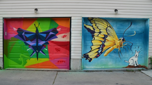 a mural on a garage door in an alley, part of butterflyways project - two adjacent garage doors, the left one is a stylized (cubist) butterfly in blues and purples. On the right is a Nick Sweetman yellow butterfly with black details as well as a white Scottie dog that looks like Tintin's dog Snowy