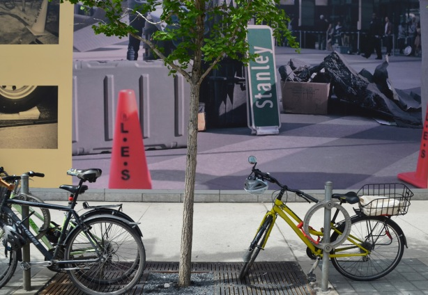 bikes parked in front of a large photo mounted on the side of the TIFF lightbox building, showing an orange movie shoot cone and a fake city street sign.