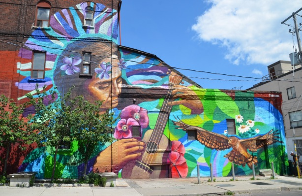 large mural by Tilay and Aner - a woman with flowers in her hair is playing a guitar, an owl in flight and some white daisies.
