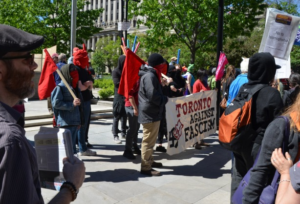 a group of people with red and black bandanas over their faces, holding a banner that says Toronto agaist fascism