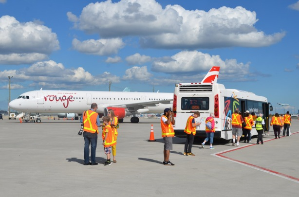 a group of people in orange safety vests standing by a bus parked on the tarmac at an airport.  Many of them are taking pictures, an Air Canada Rouge aircraft is parked behind.