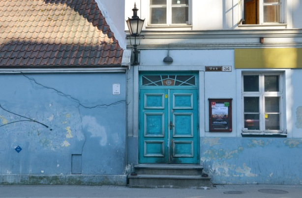 turquoise wooden double door with two steps up to it, on a house painted blue (lower part) and white (upper part).