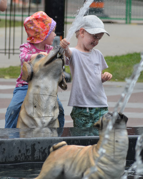 two little kids playing in a fountain, a young girl and a young boy. The boy is spraying water while the girl watches