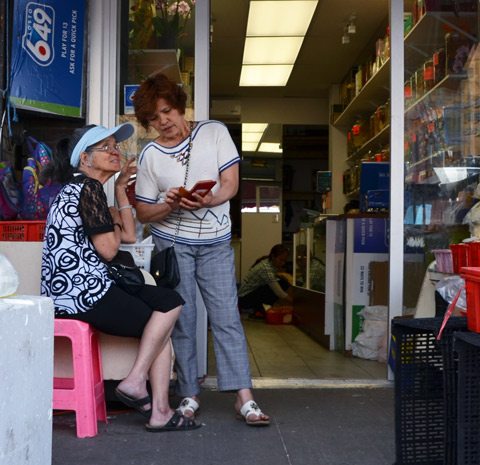 two women outside a store,looking at a phone, a woman inside is crouched on the floor, working.