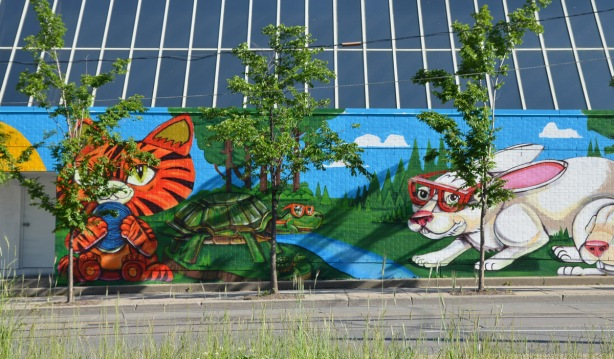3 small trees in front of a colourful mural by Uber5000 of animals, a green turtle by a blue creek, a white rabbit with red sunglasses and an orange tigerstriped kitten on the side of the THS building