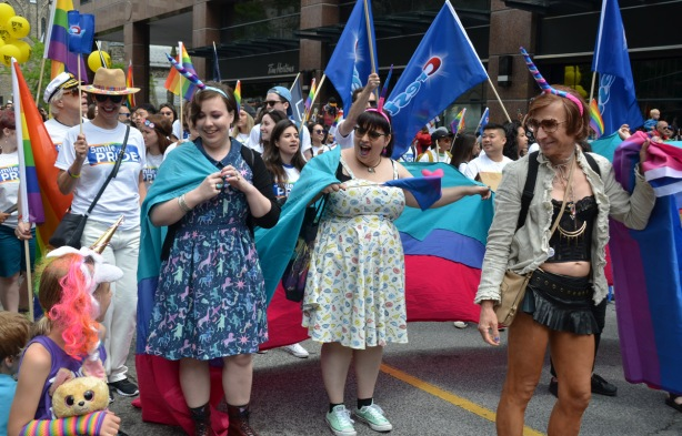 three women walking in the pride parade with a turquoise, blue and pink banner, and unicorn horns on their head, stop to talk to a young girl who also has a unicorn horn on her head