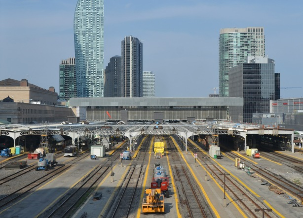 union station as seen from the west, from the skywalk, with open air tracks as well as the covered platforms. New roof over the platforms, tall buildings in the background