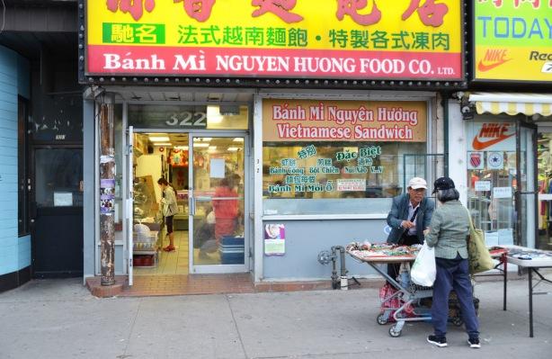 a man sells items outside a Vietnamese restaurant