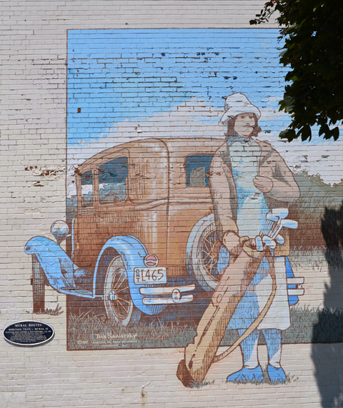 mural, woman from the 1930's standing behind a vintage car and holding a set of golf clubs
