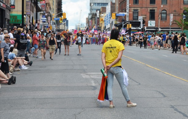 a volunteer wearing a yellow tshirt stands in the middle of yonge street facing the dyke march parade that has stopped just up the street, people are lining the sidewalks to watch the march